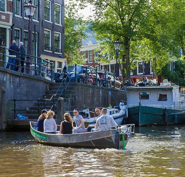 Bootje met 6 mensen van Canal Motorboats op de Amsterdamse grachten